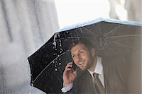 people with umbrellas in the rain - Businessman talking on cell phone under umbrella in rain Stock Photo - Premium Royalty-Freenull, Code: 6113-06899529