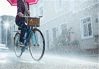 people with umbrellas in the rain - Woman riding bicycle with umbrella in rainy street Stock Photo - Premium Royalty-Freenull, Code: 6113-06899535