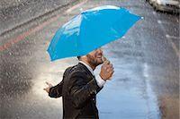 people with umbrellas in the rain - Businessman with tiny umbrella walking in rain Stock Photo - Premium Royalty-Freenull, Code: 6113-06899543