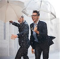 people with umbrellas in the rain - Happy businessmen with umbrellas walking in rain Stock Photo - Premium Royalty-Freenull, Code: 6113-06899544
