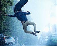 Man with umbrella jumping in rain Stock Photo - Premium Royalty-Freenull, Code: 6113-06899560