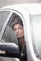 Businesswoman in car looking up at rain Stock Photo - Premium Royalty-Freenull, Code: 6113-06899562