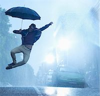 people with umbrellas in the rain - Enthusiastic man with umbrella jumping in rain Stock Photo - Premium Royalty-Freenull, Code: 6113-06899566
