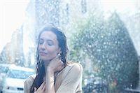 Serene woman standing in rain Stock Photo - Premium Royalty-Freenull, Code: 6113-06899585