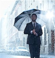Businessman under umbrella in rainy street Stock Photo - Premium Royalty-Freenull, Code: 6113-06899604