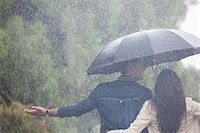 people with umbrellas in the rain - Couple walking with arms outstretched under umbrella in rain Stock Photo - Premium Royalty-Freenull, Code: 6113-06899613