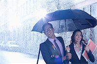 people with umbrellas in the rain - Happy businessman and businesswoman walking under umbrella in rain Stock Photo - Premium Royalty-Freenull, Code: 6113-06899614