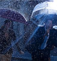 Happy business people running with umbrellas in rain Stock Photo - Premium Royalty-Freenull, Code: 6113-06899615