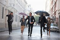 people with umbrellas in the rain - Business people with umbrellas running in rainy street Stock Photo - Premium Royalty-Freenull, Code: 6113-06899628