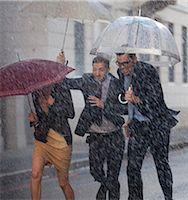 people with umbrellas in the rain - Happy business people with umbrellas running in rainy street Stock Photo - Premium Royalty-Freenull, Code: 6113-06899630