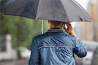 Man talking on cell phone under umbrella in rain Stock Photo - Premium Royalty-Freenull, Code: 6113-06899640