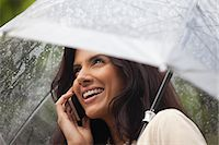 people with umbrellas in the rain - Happy woman talking on cell phone under umbrella in rain Stock Photo - Premium Royalty-Freenull, Code: 6113-06899642
