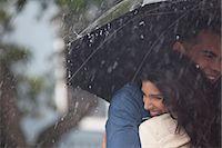 Happy couple hugging under umbrella in rain Stock Photo - Premium Royalty-Freenull, Code: 6113-06899644