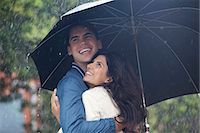 people with umbrellas in the rain - Happy couple hugging under umbrella in rain Stock Photo - Premium Royalty-Freenull, Code: 6113-06899647