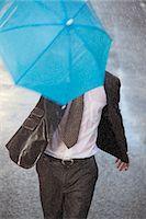 Businessman with tiny umbrella running in rainy street Stock Photo - Premium Royalty-Freenull, Code: 6113-06899661