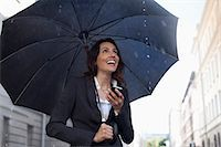 people with umbrellas in the rain - Happy businesswoman text messaging with cell phone under umbrella in rain Stock Photo - Premium Royalty-Freenull, Code: 6113-06899663