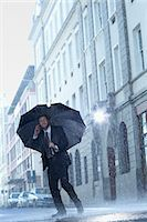 people with umbrellas in the rain - Businessman talking on cell phone under umbrella in rainy street Stock Photo - Premium Royalty-Freenull, Code: 6113-06899668
