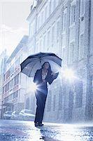 people with umbrellas in the rain - Businesswoman standing under umbrella in rainy street Stock Photo - Premium Royalty-Freenull, Code: 6113-06899669