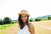 Portrait of teenaged girl standing in field, wearing straw hat, smiling at camera, Germany Stock Photo - Premium Royalty-Freenull, Code: 600-06899843