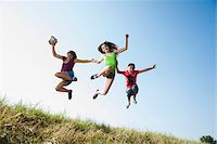Girls jumping in mid-air over field, Germany Stock Photo - Premium Royalty-Freenull, Code: 600-06899866