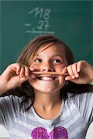 Portrait of girl standing in front of blackboard in classroom, holding pencil over mouth, Germany Stock Photo - Premium Royalty-Freenull, Code: 600-06899883