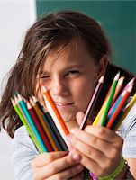 Close-up of girl holding colored pencils in hands, Germany Stock Photo - Premium Royalty-Freenull, Code: 600-06899885