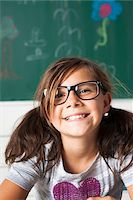 preteen girl - Close-up portrait of girl sitting at desk in classroom, Germany Stock Photo - Premium Royalty-Freenull, Code: 600-06899898