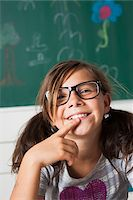 preteen girl pigtails - Close-up portrait of girl sitting at desk in classroom, Germany Stock Photo - Premium Royalty-Freenull, Code: 600-06899899