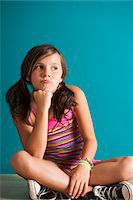 Portrait of girl sitting on floor, pouting, Germany Stock Photo - Premium Royalty-Freenull, Code: 600-06899902