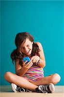Girl sitting on floor looking at smartphone, Germany Stock Photo - Premium Royalty-Freenull, Code: 600-06899904
