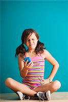 preteen girl pigtails - Girl sitting on floor looking at smartphone, Germany Stock Photo - Premium Royalty-Freenull, Code: 600-06899905