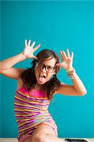 preteen girl pigtails - Portrait of girl sitting on floor making funny faces, Germany Stock Photo - Premium Royalty-Freenull, Code: 600-06899910