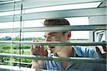 Close-up of young man looking through blinds on window, Germany Stock Photo - Premium Royalty-Free, Artist: Uwe Umstätter, Code: 600-06899992