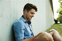 Young man sitting next to wall of building outdoors, with headphones around neck and looking at cell phone, Germany Stock Photo - Premium Royalty-Freenull, Code: 600-06900003