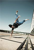 Teenaged boy doing handstand on cement road, freerunning, Germany Stock Photo - Premium Royalty-Freenull, Code: 600-06900022