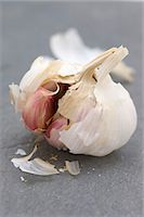 An opened garlic bulb on a slate surface Stock Photo - Premium Royalty-Freenull, Code: 659-06901569