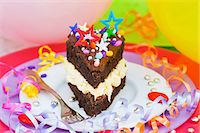 streamer - A piece of chocolate cake with colorful sprinkles and candy decorations for a party Stock Photo - Premium Royalty-Freenull, Code: 659-06902168