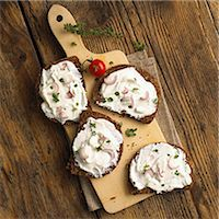 food - Slices of whole grain bread with quark and onions on a wooden board (top view) Stock Photo - Premium Royalty-Freenull, Code: 659-06902343