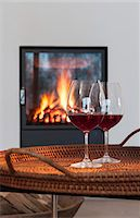 Two glasses of red wine on a table in front of a fireplace Stock Photo - Premium Royalty-Freenull, Code: 659-06902473