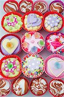 overview o of coloured cup cakes in red and pink plastic cake covers decorated with hearts, lips and sweets Stock Photo - Premium Royalty-Freenull, Code: 659-06903182