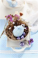 An egg decorated with a ribbon, dried flowers and chocolate eggs in an Easter nest made of moss and grass Stock Photo - Premium Royalty-Freenull, Code: 659-06903498