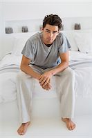 Man sitting on the bed Stock Photo - Premium Royalty-Freenull, Code: 6108-06904568