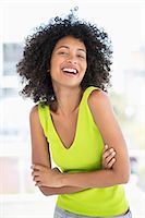 Woman standing with her arms crossed and smiling Stock Photo - Premium Royalty-Freenull, Code: 6108-06904797