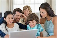 preteen long hair - Family looking at a laptop Stock Photo - Premium Royalty-Freenull, Code: 6108-06904829