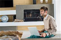 sweater and fireplace - Man using a laptop at home Stock Photo - Premium Royalty-Freenull, Code: 6108-06904848