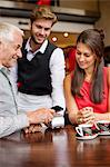 Waiter showing credit card reader to a couple on a table in a restaurant Stock Photo - Premium Royalty-Free, Artist: Blend Images, Code: 6108-06905047