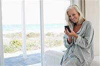 Smiling woman using a mobile phone Stock Photo - Premium Royalty-Freenull, Code: 6108-06905081