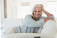 Portrait of a smiling woman sitting on a couch Stock Photo - Premium Royalty-Freenull, Code: 6108-06905119