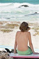 Boy sitting on the beach Stock Photo - Premium Royalty-Freenull, Code: 6108-06905211