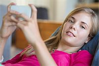 Portrait of a girl using a mobile phone and smiling Stock Photo - Premium Royalty-Freenu
